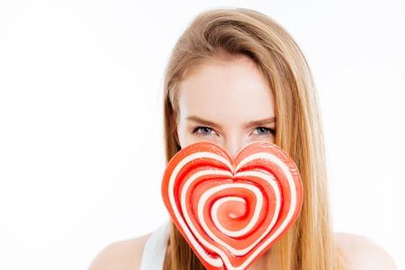 donna innamorata: Carino bella giovane donna coperto il viso con Heatr lecca-lecca a forma su sfondo bianco