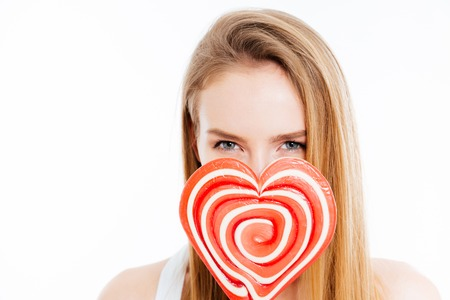 woman in love: Cute lovely young woman covered face with heatr shaped lollipop over white background