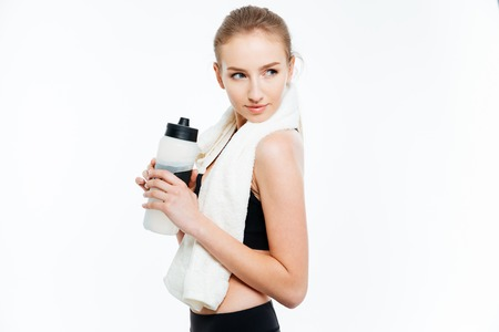 white towel: Attractive young woman athlete holding bottle of water and white towel over white background