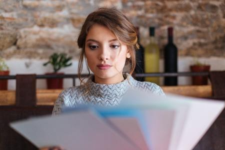 choosing: Beautiful woman choosing paper for drawing