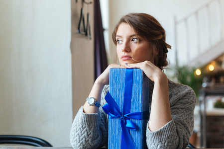spontaneous expression: Thoughtful woman sitting at the table with gift box and looking away