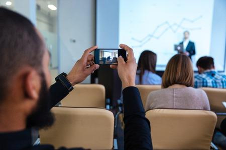 groups of people: Vista posterior de un joven africano que hace el vídeo con el teléfono inteligente en conferencia de negocios en la sala de reuniones Foto de archivo