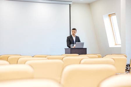 the thoughtful: Thoughtful businessman writing speech on laptop in empty conference hall Stock Photo