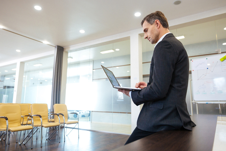 Focused serious businessman preparing for presentation using laptop in empty meeting room