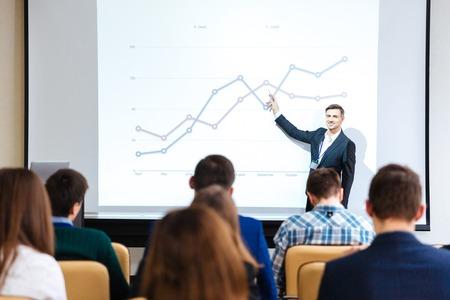 Sonriente que se coloca el altavoz guapo y gráficos que explican en conferencia de negocios en sala de reunión