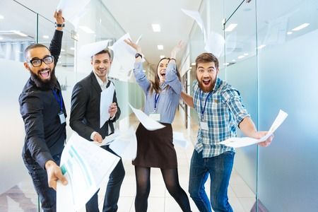 Group of joyful excited business people throwing papers and having fun in office Standard-Bild