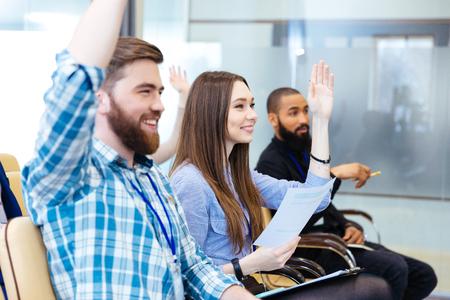 Jeunes gais assis avec les mains levées et poser des questions sur la conférence d'affaires