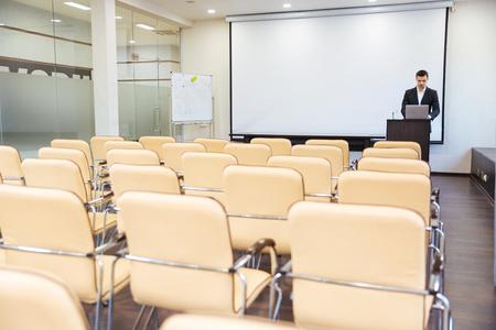 Serio hermoso del altavoz para preparar la conferencia usando la computadora portátil en sala de juntas vacía