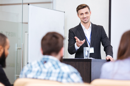 Cheerful speaker standing at the tribune in conference hall and pointing on male in audience Stock Photo