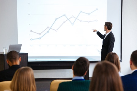 altoparlante sicuro che dà presentazione pubblica utilizzando proiettore in sala conferenze