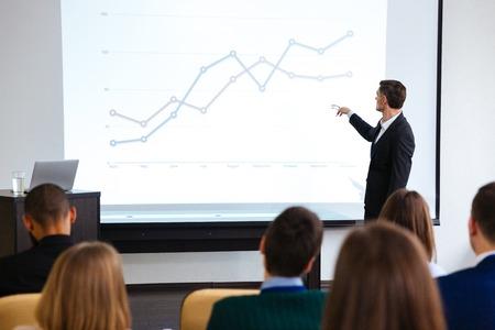 Zelfverzekerd spreker geven publieke presentatie met projector in conferentieruimte