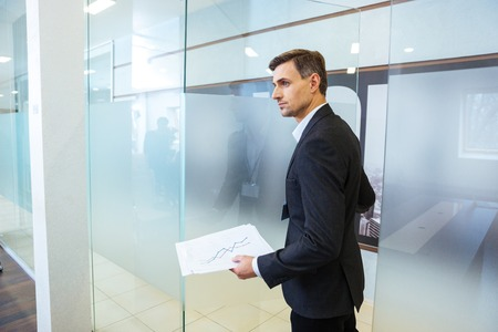 Confident businessman in formalwear holding documents and entering the office Foto de archivo