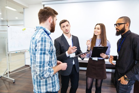 lady boss: Head of department standing and talking to smiling young employees in office