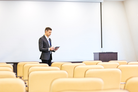 Handsome concentrated speaker repeating his speech and using tablet in empty boardroom Imagens - 52193322