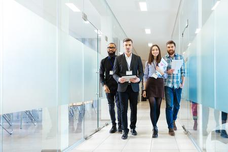 juntos: Comprimento cheio do grupo de executivos novos felizes andando pelo corredor no escritório junto