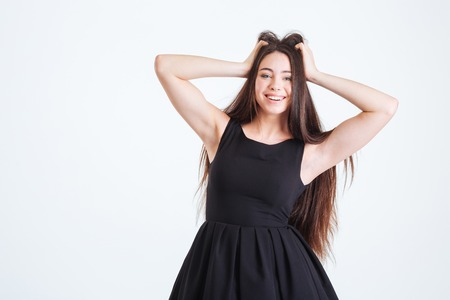 streight: Happy charming young woman in black dress standing and touching her beautiful dark long hair over white background