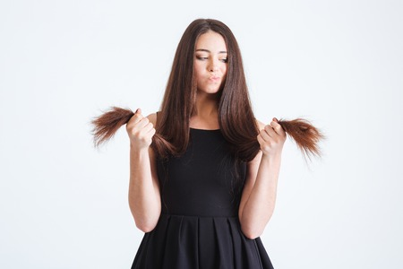Upset beautiful young woman standing and looking on splitting ends of her long dark hair over white background