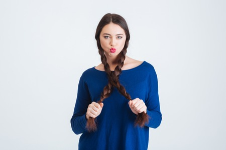 kissing lips: Cute lovely young woman holding her two long dark braids and making duck face over white background