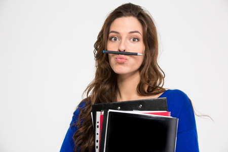 comical: Amusing comical young woman holding folders and making funny face with pen over white background Stock Photo