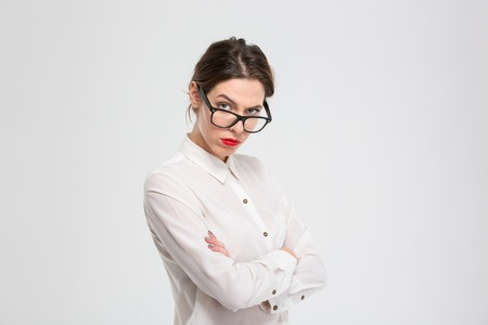 angry boss: Angry businesswoman in glasses looking at camera isolated on a white background Stock Photo