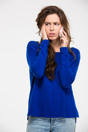 spontaneous expression: Sad woman talking on the phone isolated on a white background Stock Photo