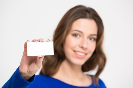 beautiful smile: Smiling pretty young woman holding and showing blank card over white background