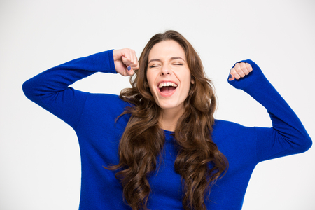 Ecstatic excited successful young woman with raised hands celebrating victory over white background