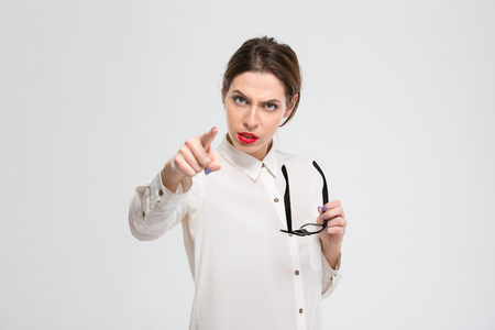 Angry businesswoman pointing finger at camera isolated on a white background