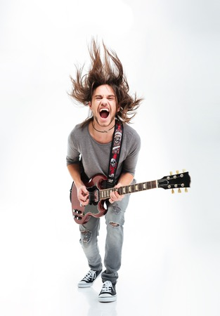 Crazy young man shaking head and playing electric guitar over white background