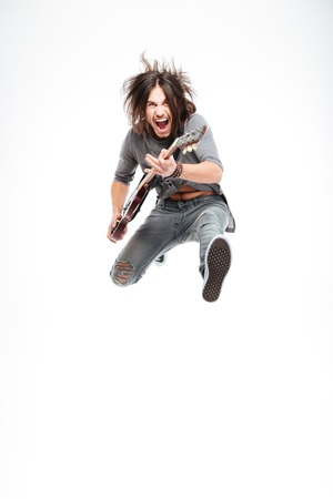 Excited joyful young male guitarist with electric guitar shouting and jumping over white background
