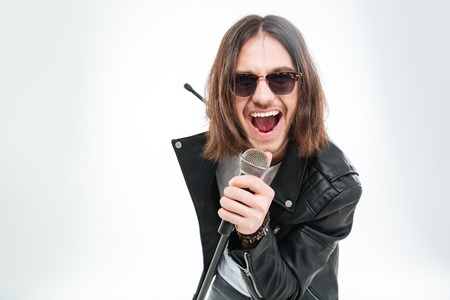 Happy young man with long hair in sunglasses using microphone for singing over white background Reklamní fotografie