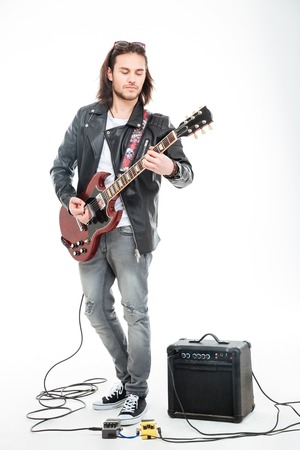 Concntrated young male guitarist playing electric guitar and using amplifier over white background