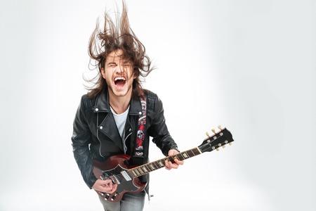 Emocionado el joven en la chaqueta de cuero negro, con júbilo la guitarra eléctrica y sacudir la cabeza sobre el fondo blanco