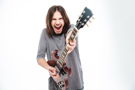 headbang: Excited popular young male singer with long hair shouting and playing electric guitar over white background Stock Photo
