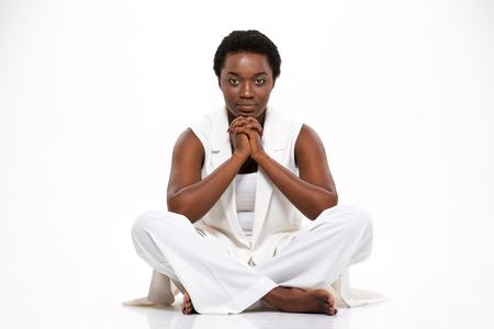 legs crossed: Thoughtful serious african american young woman sitting with legs crossed over white background Stock Photo