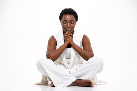 Nachdenklich ernst African American junge Frau sitzt mit gekreuzten Beinen auf weißem Hintergrund