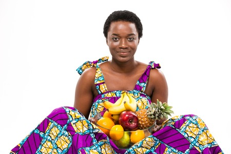 sundress: Cheerful beautiful african american young woman in bright sundress sitting and holding different exotic fruits over white background Stock Photo
