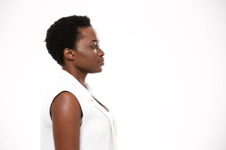 african women: Profile of beautiful serious african american young woman with short haircut over white background