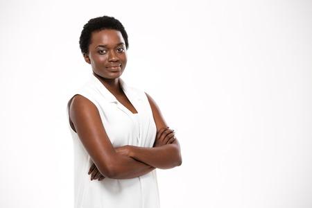 Lächelnd zuversichtlich African American junge Frau stand mit verschränkten Armen auf weißem Hintergrund