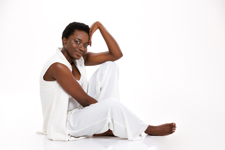 african american woman: Beautiful happy african american young woman sitting on the floor barefoot over white background