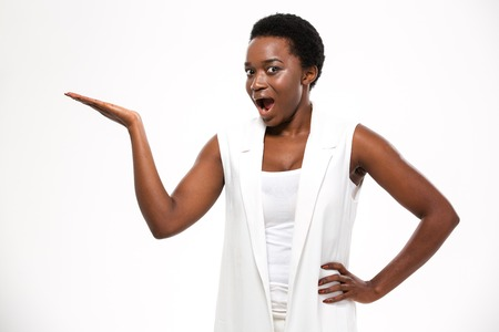 wondered: Wondered excited african american young woman standing and holding copyspce on palm over white background