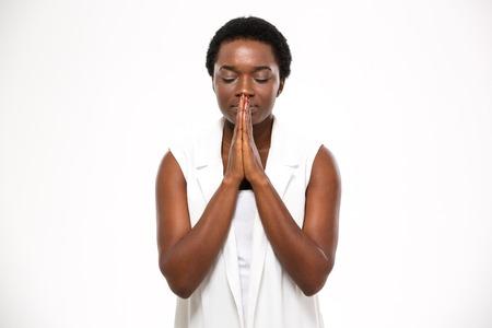 Hermosa hermosa joven afroamericana de pie y rezando sobre fondo blanco Foto de archivo