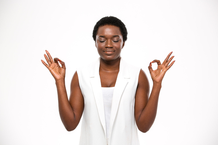 women sport: Peaceful attractive african american young woman meditating and keeping calm over white background