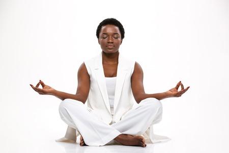 De vreedzame vrij Afrikaanse Amerikaanse jonge vrouwenzitting en het mediteren in lotusbloem stellen over witte achtergrond