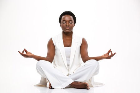 Pacified pretty african american young woman sitting and meditating in lotus pose over white background