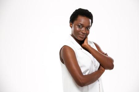 흰색 배경 위에 접혀 손으로 서 챠밍 행복 한 아프리카 계 미국인 젊은 여자