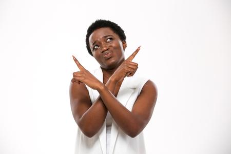 Confused african american jeune femme pointant vers le haut avec les deux mains sur fond blanc Banque d'images