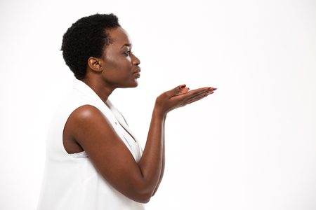 kissing lips: Profile of charming african american young woman sending a kiss over white background