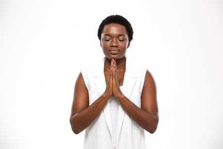 Calm pretty african american young woman with closed eyes standing and meditating over white background
