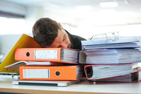 Businessman sleeping on the folders in office